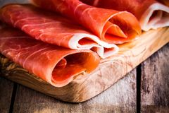 Thin slices of prosciutto closeup on a cutting board royalty free stock photo