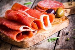 Thin slices of prosciutto with olives and salami on a cutting board royalty free stock image