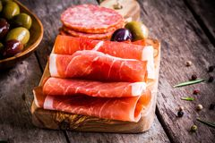 Thin slices of prosciutto with olives and salami on a cutting board stock photography