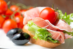 Thin slices of prosciutto on plate Stock Photo