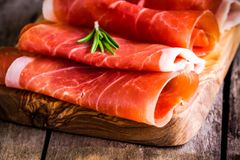 Thin slices of prosciutto with rosemary closeup on a cutting board royalty free stock image