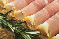 Thin slices of prosciutto with rosemary on wooden cutting board,vintage background. Stock Photo