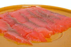 Thin slices of red fish lie on a plate Stock Photography