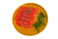 Thin slices of red fish lie on a plate Stock Images