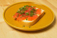 Thin slices of red fish lie on white bread Stock Photos