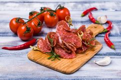 Thin slices of salami. On a wooden stick with spices and vegetables. Selective focus stock photo