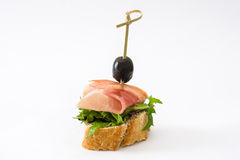 Thin slices spanish serrano ham skewer with olive and lettuce isolated on white background Royalty Free Stock Photos