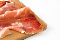 Thin slices of spanish serrano ham on a table isolated on white background Stock Photos