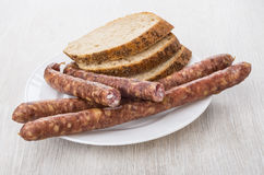 Thin smoked sausages and pieces of bread in white plate Stock Images