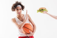 Thin sportsman dislikes fat sandwich. Slim young man is refusing to eat unhealthy food. He is raising hand opposite burger and looking at camera with aversion Royalty Free Stock Image