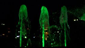 Green colour streams of water in fountain at night time, super slow motion. Thin streams of water colorful fountain with green bright illumination against the stock video