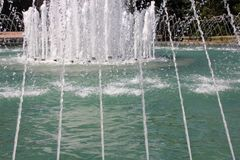 Thin streams of water on the fountain. Drops of water and fresh streams of moisture. Stock Photos