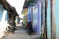 Thin street with colorful houses and motorbikes Stock Images