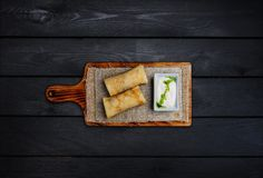 Thin stuffed pancakes or russian blini with sour cream. On a wooden board. Top view. Black wooden background royalty free stock images