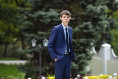 A thin tall guy with sticking ears walks in the park, dressed in a classic blue suit, keeps his hands in his pockets. A thin tall guy with sticking ears walks Royalty Free Stock Image