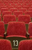 Thin theatre. Empty red wooden cinema/theater seats, number 13 in the middle Stock Images