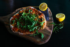Thin turkish pizza with minced meat, lemon and arugula Stock Images