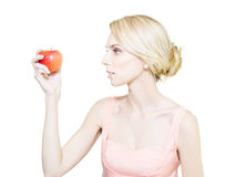 Thin undernourished woman holding an apple. Pale thin undernourished woman whos fading away holding tempting ripe red apple in hand convinced that it will cause Royalty Free Stock Images