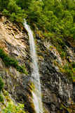Thin water stream flowing from rocky slope of Stock Photography