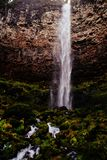 A thin waterfall dripping down a rocky terrain. A thin waterfall dripping down a rocky green surface from a steep rocky hill stock photo