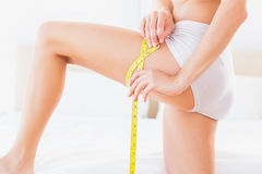 Thin woman measuring her thigh Royalty Free Stock Images