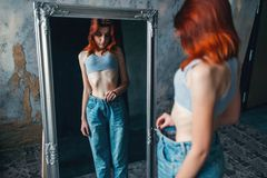 Thin woman tries on big size jeans, weight loss. Thin woman tries on big size jeans against mirror, weight loss, anorexia. Fat or calories burning concept Royalty Free Stock Images