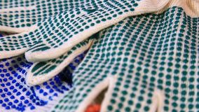 Thin work gloves with blue and green pimples on a rotating surface, stock video