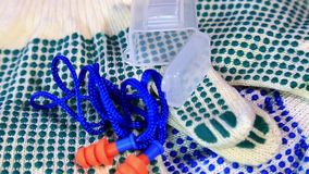 Thin work gloves with green pimples and ear plugs on a rotating surface, stock video