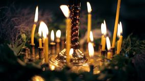 Thin yellow candles in church on a black background. Bokeh light, slide move out stock video footage