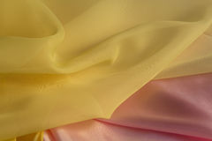 Thin yellow fabric on a pink silk Stock Photography