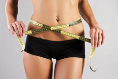 Thin young woman measures the waist Royalty Free Stock Images