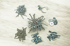Things found on a workbench. Piles of nails, screw, bolts, washers, a clamp, rivets, and misc. things found on a workbench shot flat lay from overhead on wood Stock Image