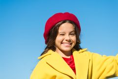 Things gonna be alright. Girl wink cheerful face blue sky background. Kid girl wear hat and coat cheerful satisfied with. Everything. Cheerful mood positive royalty free stock photo