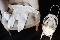 Things for the newborn baby lie on the chair. Nearby there is a stock photography