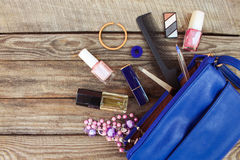 Things from open lady handbag. Women's purse on wood background. Cosmetics and women's accessories fell out of the blue handbag. Toned image Stock Images