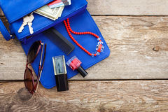 Things from open lady purse. Cosmetics, money and women`s accessories fell out of blue handbag. Top view Royalty Free Stock Photos