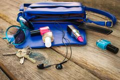 Things from open lady purse. Cosmetics and women`s accessories fell out of blue handbag Royalty Free Stock Photo