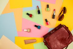 Things from open lady purse. Cosmetics and women`s accessories fell out of red handbag Stock Photos