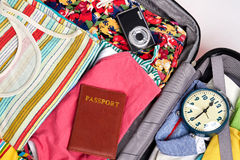 Things for sea abroad. Beach clothes, passport, camera, alarm clock in opened suitcase Stock Photo