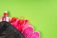 Things for sport and a bottle of water in a black bag on the corner of a green board background. Things for sport and a bottle of water in a black bag on the Royalty Free Stock Images