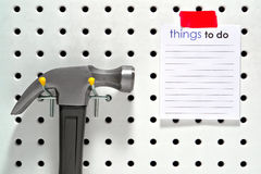 Things To Do List and Hammer on Workshop Pegboard Stock Images