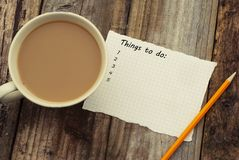 Things to do list, inscription. Blank papper and cup of coffee, over rustic wooden background, conceptual. Things to do list, inscription. Blank papper and cup stock photos