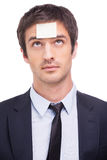 Things to do. Portrait of frustrated young man in formalwear and adhesive note on his forehead standing against white background Royalty Free Stock Image