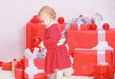 Things to do with toddlers at christmas. Christmas gifts for toddler. Gifts for child first christmas. Little baby girl. Play near pile of gift boxes. Family stock image