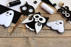 Halloween felt embellishments. Felt ghost, spider, owl embellishments on a vintage wooden table. Sewing tools and materials set. Things to make with felt sheets Royalty Free Stock Image