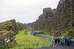 Tourists walk through the Almannagja fault line in the mid-atlantic ridge north american plate in Thingvellir National Park. Thingvellir, Iceland - July 19, 2017 royalty free stock image