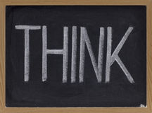 Think. The word think - big letters in white chalk on blackboard royalty free stock image
