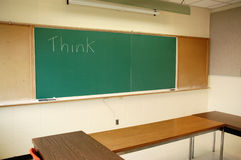 Think. Green blackboard with word think in lecture room Stock Images