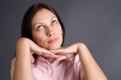 Think. Thoughtful pretty woman close-up portrait over gray concept stock photos