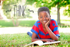 Think against little boy reading in the park Stock Photos